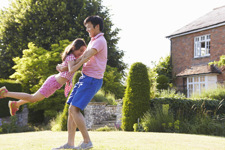 Asian Father And Daughter Playing In Summer Garden Together Stock Photo