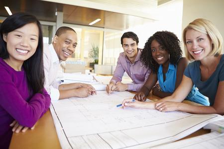 reunion de trabajo: Grupo de arquitectos discutir los planes en la oficina moderna Foto de archivo