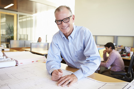 Male Architect Studying Plans In Office photo