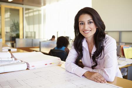 architect: Arquitecto femenino que estudia planes en la oficina Foto de archivo
