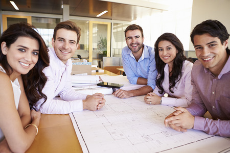 Group Of Architects Discussing Plans In Modern Office photo