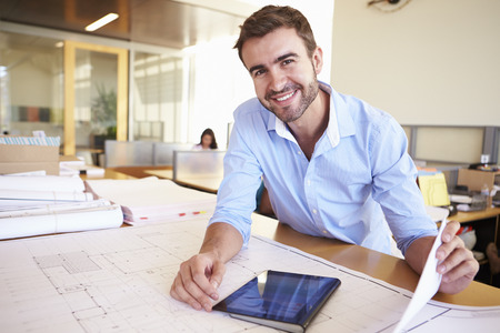 uomo felice: Architetto maschio con tavoletta digitale che studiano i programmi In Ufficio