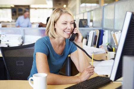 personas trabajando en oficina: Mujer en el tel�fono en la oficina ocupada Moderno
