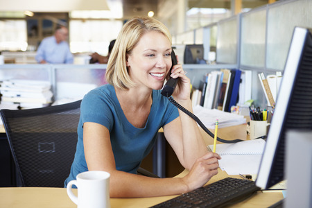 casual: Woman On Phone In Busy Modern Office Stock Photo