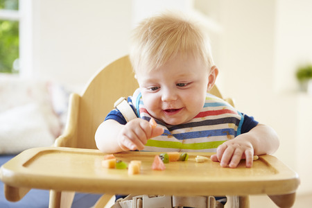 eating: Baby Boy Eating Fruit In High Chair Stock Photo