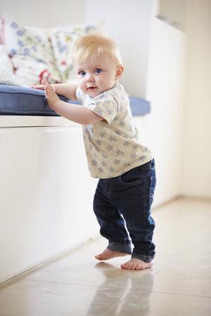 若い男の子の家具に保持することによって歩くことを学ぶ 写真素材