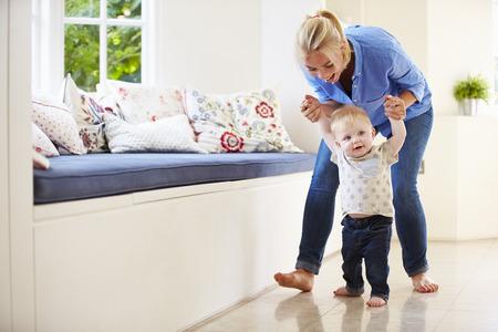 母は散歩することを学ぶ彼の若い息子を助ける 写真素材