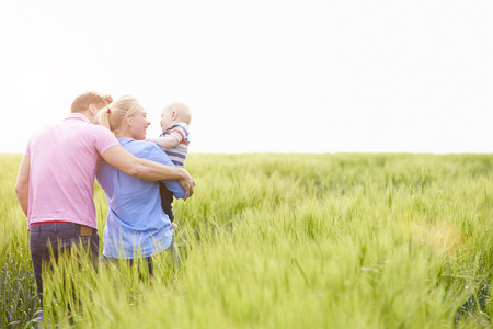family walking: Family Walking In Field Carrying Young Baby Son