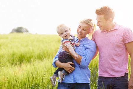 フィールドを歩く家族運ぶ若い赤ちゃんの息子