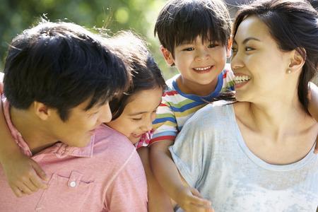 familia abrazo: Familia asi�tica disfruta de la caminata en campo del verano