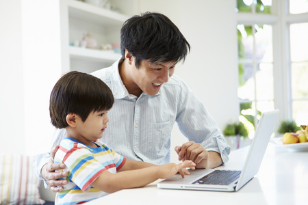 asian family home: Asian Father Helping Son To Use Laptop At Home