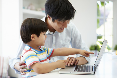 Asian Father Helping Son To Use Laptop At Home photo