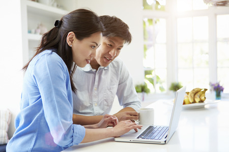 asian laptop: Asian Couple Looking at Laptop In Kitchen