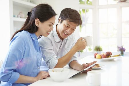 Pareja asiática que mira la tablilla digital sobre el desayuno