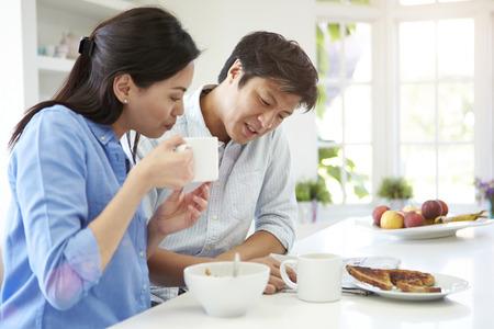 Aziatische Lezing van het Paar krant bij het ontbijt