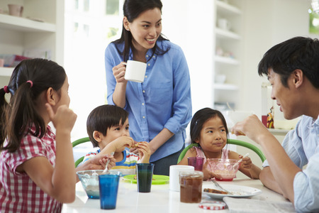 comiendo cereal: Familia asiática desayunando juntos en la cocina