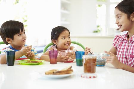 niños desayunando: Tres niños asiáticos desayunando juntos en la cocina