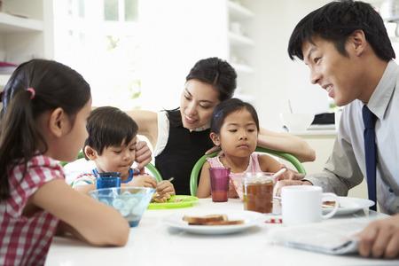 夫は仕事に行く前に朝食を持っているアジアの家族