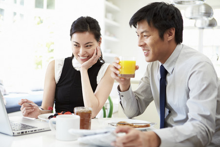 Asian Couple Looking at Laptop Over Breakfast Stock Photo
