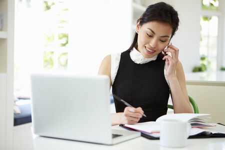 working from home: Asian Businesswoman Working From Home Using Mobile Phone Stock Photo