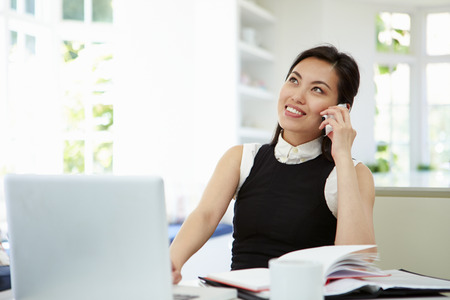 Asian Businesswoman Working From Home Using Mobile Phone photo