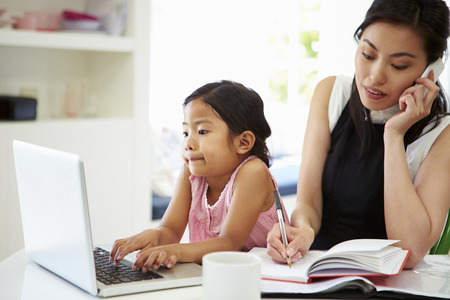 smiling mother: Busy Mother Working From Home With Daughter