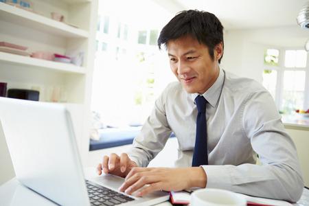 노트북에서 집에서 일하는 아시아 사업가