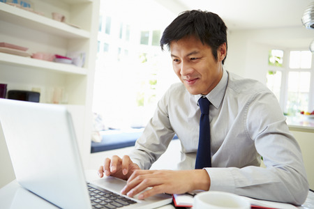 asian man: Asian Businessman Working From Home On Laptop