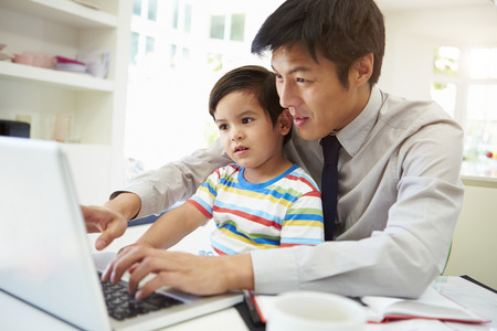working: Busy Father Working From Home With Son