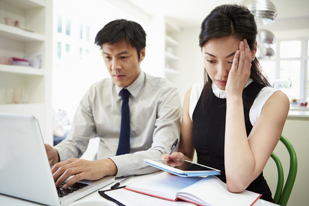 Worried Asian Couple Looking At Personal Finances Imagens
