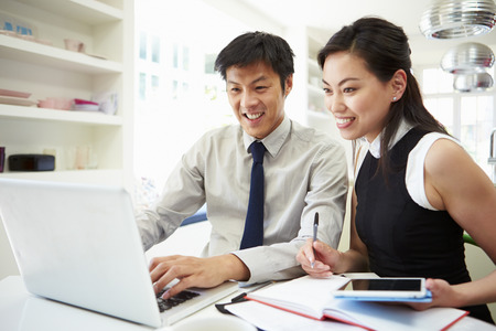 Asian Couple Working From Home Looking At Personal Finances photo