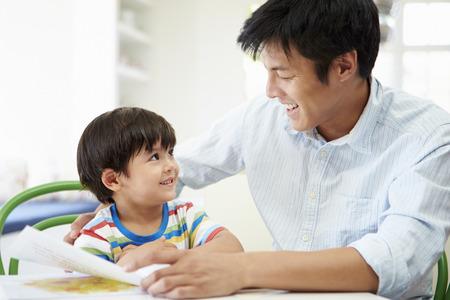 padres e hijos felices: Hijo de ayuda del padre con la preparación