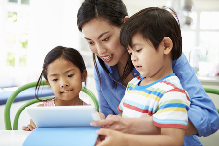helping children: Mother Helping Children With Homework Using Digital Tablet