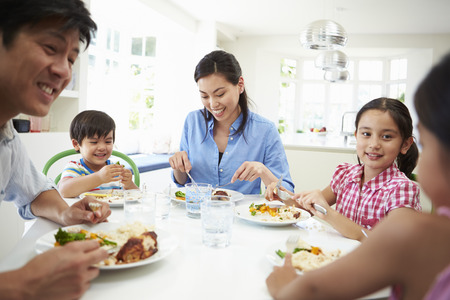 7 year old girl: Asian Family Sitting At Table Eating Meal Together Stock Photo