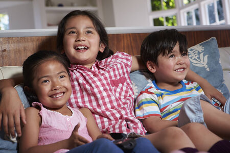 4 5 year old: Three Asian Children Sitting On Sofa Watching TV Together