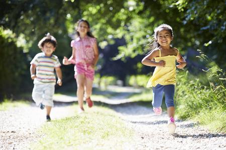 Three Asian Children Enjoying Walk In Countryside
