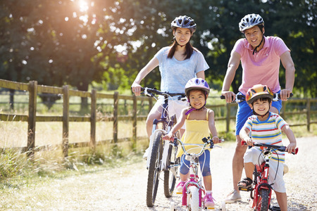 family exercise: Asian Family On Cycle Ride In Countryside Stock Photo