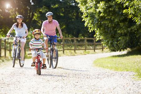 bicicleta: Familia asiática en paseo del ciclo En Campo