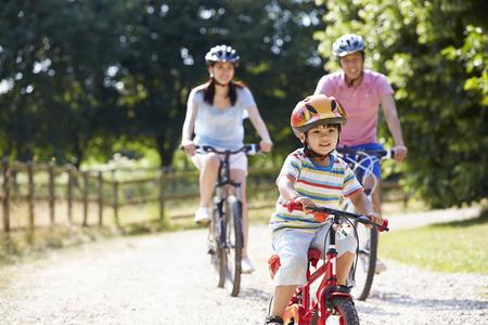 Asijské rodina na cyklu jezdit v krajině