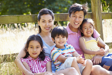 outdoors woman: Asian Family Relaxing By Gate On Walk In Countryside