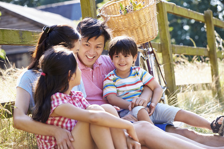 Asian Family Resting By Fence With Old Fashioned Cycle photo