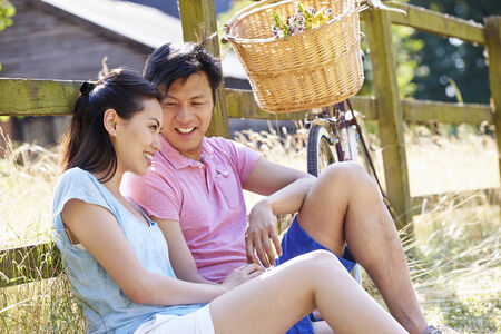Asian Couple Resting By Fence With Old Fashioned Cycle photo