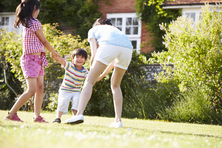 Asian Mother Playing In Summer Garden With Children photo