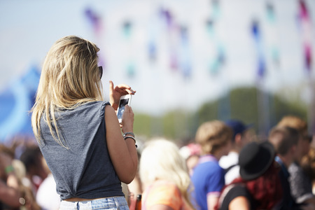 crowd: Young Woman At Outdoor Music Festival Using Mobile Phone
