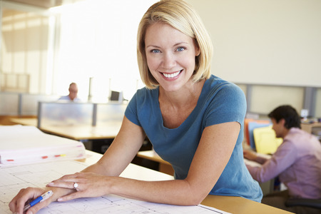 charming business lady: Female Architect Studying Plans In Office