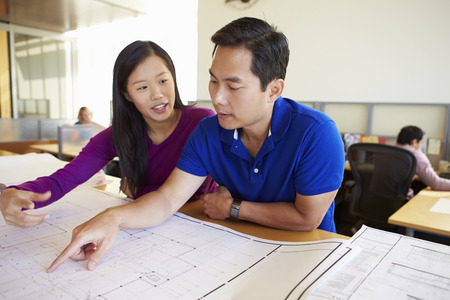 Architects Studying Plans In Modern Office Together photo