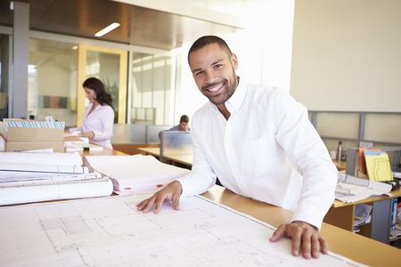 Mannelijke Architect die plannen bestuderen In Office