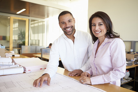 female architect: Architects Studying Plans In Modern Office Together