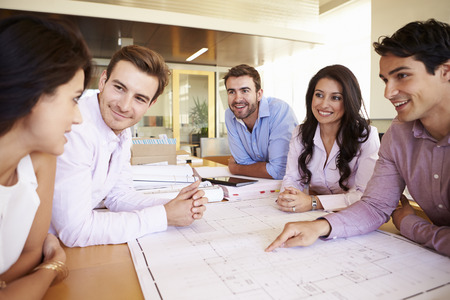 empleados trabajando: Grupo de arquitectos discutir los planes en la oficina moderna Foto de archivo