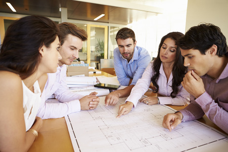 architect office: Group Of Architects Discussing Plans In Modern Office